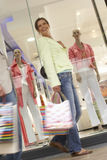 Couple with shopping bags walking past window display in shop, low angle view (blurred motion, tilt) Royalty Free Stock Images