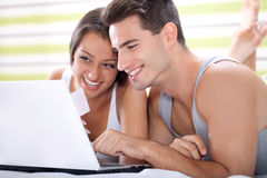 Couple shopping in bed Stock Photography