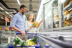 Couple with shopping cart buying food at grocery. Sale, consumerism and people concept - happy couple with shopping cart buying frozen food at grocery store or Royalty Free Stock Photography