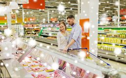 Couple with shopping cart buying meat at grocery Stock Photography
