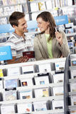 Couple shopping for CDs in record shop, standing in aisle behind rack, smiling, man showing woman CD (tilt) Stock Image