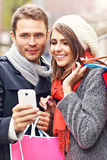 Couple shopping in the city with smartphone Stock Photo