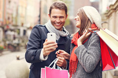 Couple shopping in the city with smartphone Royalty Free Stock Photos