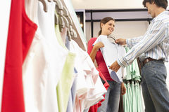 Couple shopping in clothes shop, man holding pale blue top up against girlfriend, smiling, side view Royalty Free Stock Image