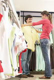 Couple shopping in clothes shop, woman holding yellow top up against boyfriend, smiling, side view, surface level Royalty Free Stock Images