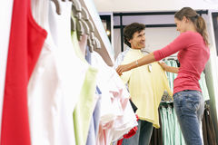 Couple shopping in clothes shop, woman holding yellow top up against boyfriend, smiling, side view Royalty Free Stock Images
