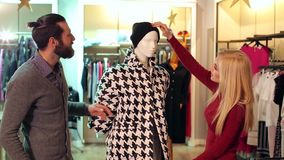 Couple is shopping at a clothing store, they look at the coat on the mannequin. stock video footage