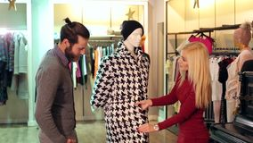 Couple is shopping at a clothing store, they look at the coat on the mannequin. The couple is shopping at a clothing store, they look at the coat on the stock video footage