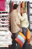 Couple shopping for cushions in department store, woman placing hand on man's shoulder, smiling Stock Photos