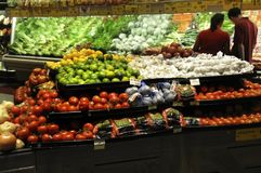 Couple shopping in the  fruit and vegetable section of a store royalty free stock photo