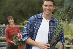 Couple shopping in garden centre, focus on man holding pot plant in foreground, smiling, portrait Stock Photography