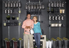Couple shopping in garden centre, man carrying watering can, indoors, portrait Stock Image