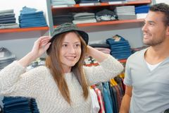 Couple shopping for hats. Afford Stock Photo