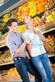 Couple with shopping list against the piles of fruits Stock Images