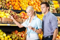 Couple with shopping list against the stacks of fruits Royalty Free Stock Photos