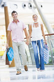 Couple shopping in mall. Carrying bags Royalty Free Stock Images