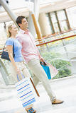 Couple shopping in mall. Carrying bags Stock Photography