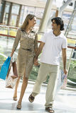 Couple shopping in mall. Carrying bags Royalty Free Stock Photos