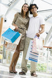 Couple shopping in mall. Carrying bags Royalty Free Stock Photo