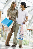 Couple shopping in mall. Carrying bags Royalty Free Stock Image