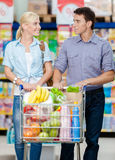 Couple in the shopping mall with cart full of food Royalty Free Stock Images
