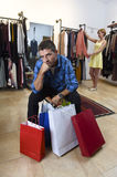 Couple shopping with man tired and bored holding bags and woman happy looking for dress Royalty Free Stock Photo