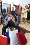 Couple shopping with man tired and bored holding bags and woman happy looking for dress Stock Images