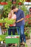 Couple shopping in a nursery shop. Happy couple shopping together in a nursery shop stock image