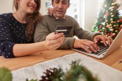 Couple shopping online for christmas with credit card and laptop Royalty Free Stock Images