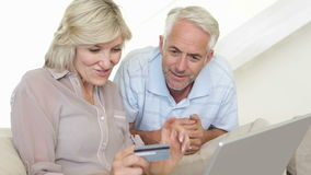 Couple shopping online on the couch stock footage