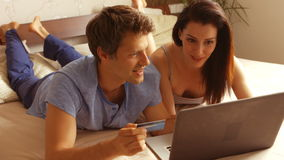 Couple shopping online on laptop using credit card. On bed in bedroom 4k stock footage