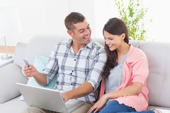 Couple shopping online on laptop using credit card. Happy couple shopping online on laptop using credit card at home Royalty Free Stock Photography