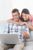 Couple shopping online through laptop using debit card Royalty Free Stock Photos