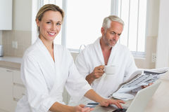 Couple shopping online and reading newspaper in bathrobes Royalty Free Stock Images