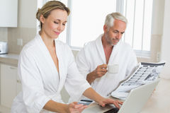 Couple shopping online and reading newspaper in bathrobes Stock Images