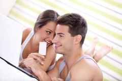 Couple shopping online. Young couple shopping online in bedroom Royalty Free Stock Photos