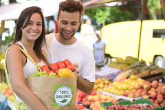 Couple shopping at open street market. Stock Photos