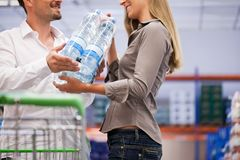 Couple Shopping for Packed Bottles Stock Images