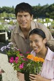 Couple Shopping at Plant Nursery holding flowers portrait Stock Photos