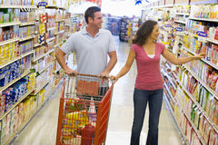 Couple shopping in supermarket. Couple in shopping in supermarket grocery aisle Royalty Free Stock Photography