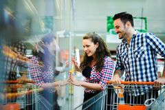 Couple shopping in supermarket while carrying shopping cart royalty free stock photography