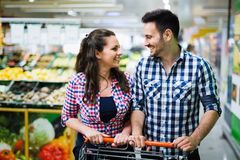 Couple shopping in supermarket while carrying shopping cart stock photo