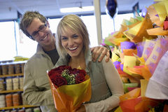 Couple shopping in supermarket, surprised woman holding flower bouquet, smiling, portrait Royalty Free Stock Images
