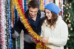 Couple Shopping For Tinsels At Store Royalty Free Stock Image
