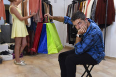 Couple shopping together with man waiting bored frustrated while girl is fitting clothes. Young couple shopping together with men sitting and waiting bored and Royalty Free Stock Images