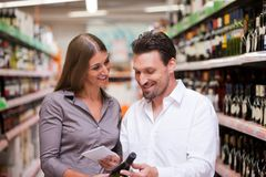 Couple Shopping for Wine at Supermarket Royalty Free Stock Image
