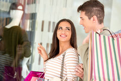Couple In Shopping. Young happy couple in shopping passes in front of window shopping mall carrying bags in their hands, looking in shop window Royalty Free Stock Image