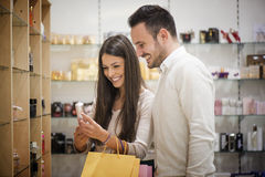 Couple in shopping. A young couple sharing a laugh while shopping in a cosmetics store.They are buying a perfume stock photos