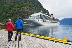 Couple on the shore of the fjord looks at a cruise liner, Norway Royalty Free Stock Photos