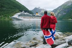 Couple on the shore of the fjord looks at a cruise liner, Norway. Sea cruise in Norway. Couple of travelers with a Norwegian flag look at the Cruise liner. Fjord royalty free stock photos